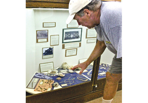 Joe Townsend shows off the Southold Indian Museum's collection in 2012. (Credit: Beth Young, file)