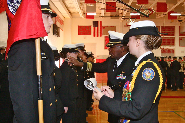 Commander Jimmie Miller with Lt. Julie Dickerson measures everything on the uniform as Lt. Dickerson records it.