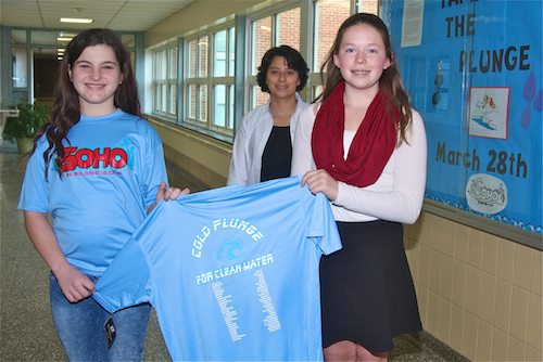 Seventh grade students Amanda Bardsley and Elizabeth Jernick (right) hold up a cold plunge t-shirt as English teacher Emilia Dakis watches on. (Credit: Barbaraellen Koch)