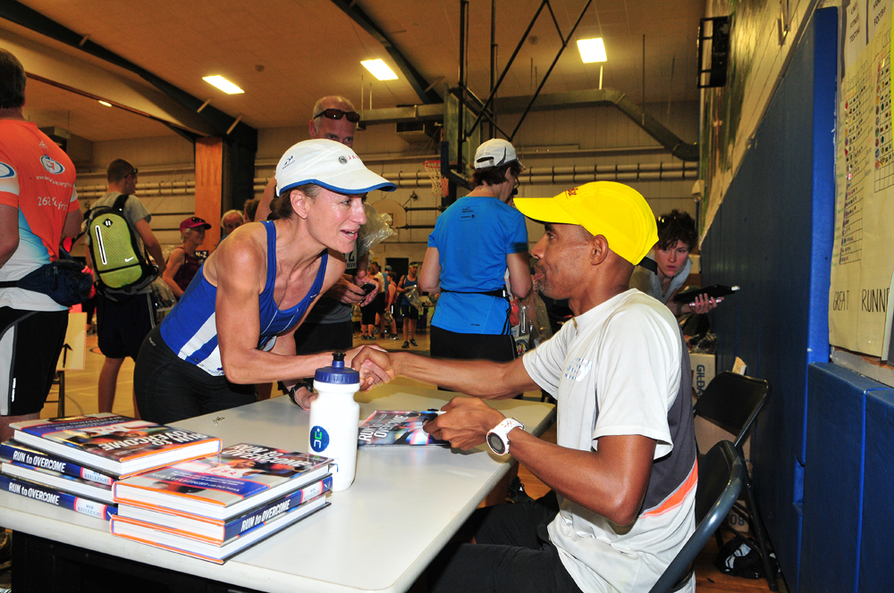 Boston Marathon winner Meb Keflezighi autographs copies of his book prior to the race. (Credit: Bill Landon)