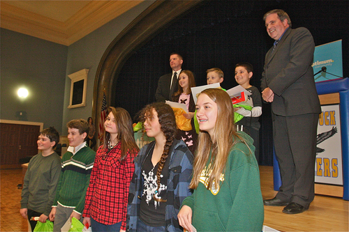 """BARBARAELLEN KOCH PHOTO Supesrvisor Scott Russell (far left) with the """"Weather in 2040"""" poster contest winners (front row from left) sixth to eighth grade winners Caleb Foley, Dane Reda, Jillian Orr, Cassidy Mullin, Dorothy Condon and not pictured Gabrielle Wahlers. Back row third grade winners (from left) Leah Weir, Thomas McGunnigle and Michael Garrett with Optimum emcee Lou Brogno Wednesday afternoon at Mattituck High School."""