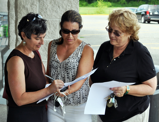 Southold Town trustee candidate Abigail Field, left, of Cutchogue signs a petition to create the Women's Equality Party line. The petition was being circulated by a group of fellow Democrats at the King Kullen in Cutchogue Sunday, including Jennifer Maertz of Rocky Point, center, and local committeewoman Lynn Summers of Southold.