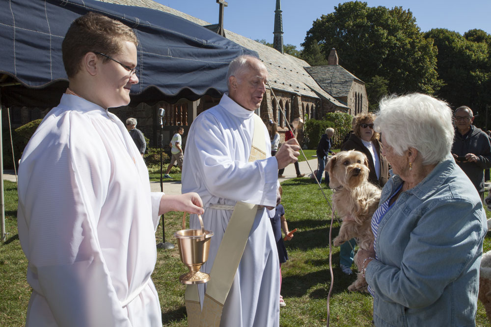 Deacon Sykes, center, blesses Eileen Peters' dog Daisy, age 6, as Chris Massey looks on.