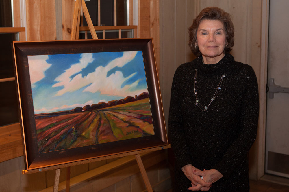 """Artist Laura Stroh of Jamesport with """"Home for the Harvest,"""" the painting she donated for auction."""