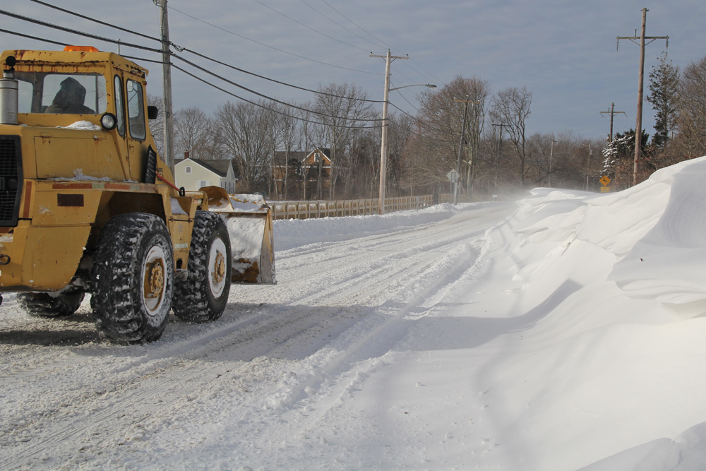 A lone dozer makes its way down Main Road in Orient, driving through one of many snow drift areas. (Credit: Carrie Miller)