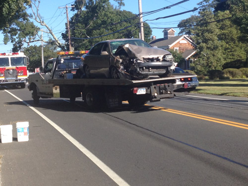 RACHEL YOUNG PHOTO | A car is towed away after its driver hit a telephone pole on Main Road today.