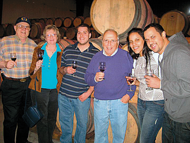 "Pindar Vineyards proprietor ""Dr. Dan"" Damianos (in purple sweater) hosts a barrel tasting and behind-the-scenes tour for Pindar Wine Club members. (Credit: Courtesy photo)"