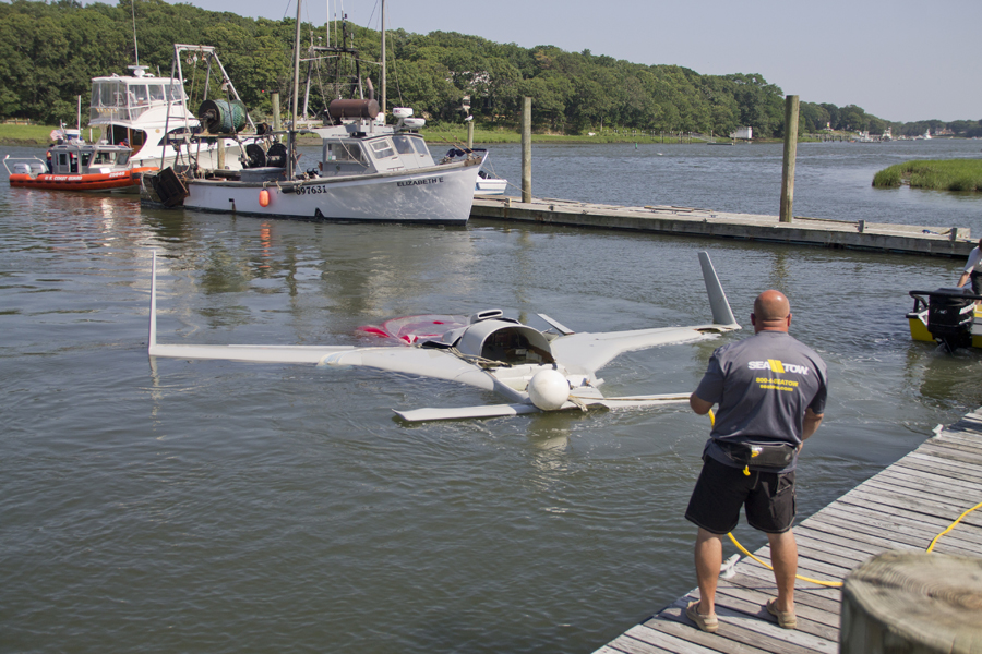 A Sea Tow helps pull the downed plane from water in Mattituck Inlet Monday afternoon. (Credit: Paul Squire)
