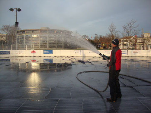 DAVID ABATELLI PHOTO | Michael Croteau, who coaches hockey on the rink on Sunday mornings, wets the Greenport Village ice rink to prep it for its opening.