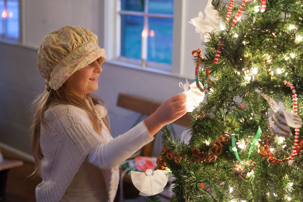Savanna Smith, 9, of Southold decorates the tree in the Bay View Schoolhouse.