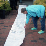 A community member places a candle onto the scroll.