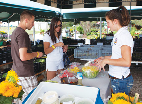 Sang Lee Farms employee Lucy Senesac, right, offers Paul and Alexandra Adinolfi of Farmingville a taste of yellow watermelon at the Peconic farm during the fifth annual North Fork Foodie Tour hosted Sunday by North Fork Reform Synagogue.